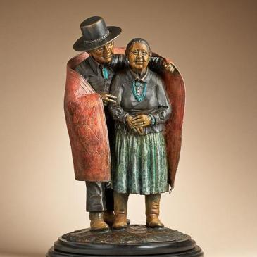 Bronze sculpture of an older man gently wrapping a blanket around an older woman by Star Liana York
