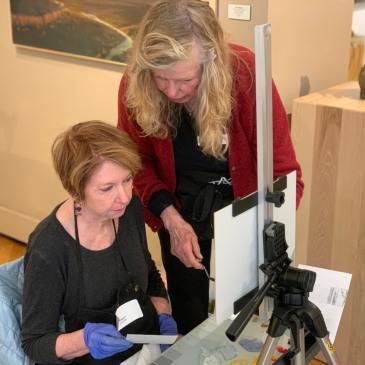 Peggy Immel assists a student at her artist workshop