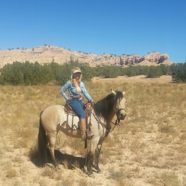 A picture of Star Liana York on her horse riding through the New Mexico landscape