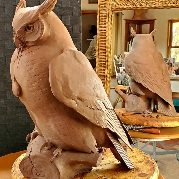 Clay sculpture being worked on in the artist's studio of an owl holding a moonstone by Star Liana York